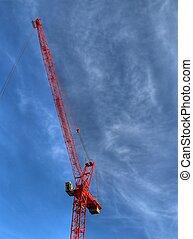 red construction crane over blue sky