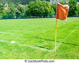 Red corner flag on soccer field at sunny day