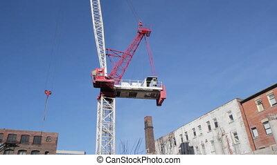 Red crane rotates. Wide.