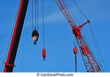 Red cranes in construction site against blue sky. ...