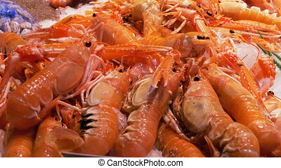Red crayfish in the ice on the counter in La Boqueria Fish...