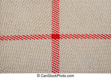 Red cross on sackcloth close up
