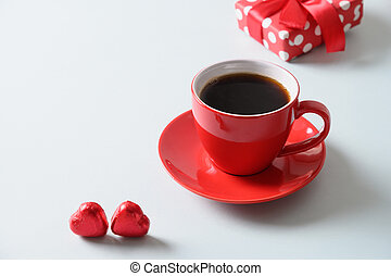 Red cup of coffee, heart sweets and gift cookies on blue background. Valentine's day.