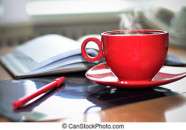 Red cup of coffee on the desk