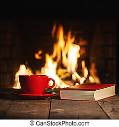Red cup of coffee or tea and old book on wooden table near  fireplace.