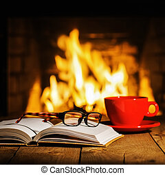 Red cup of coffee or tea, glasses and old book on wooden table near fireplace.