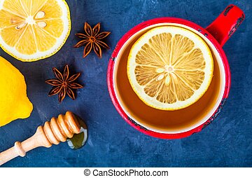 red cup of tea with lemon, honey and anise