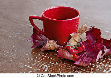 Red Cup with autumn leaves and berries