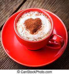 Red cup with cappuccino and heart decoration over foam....