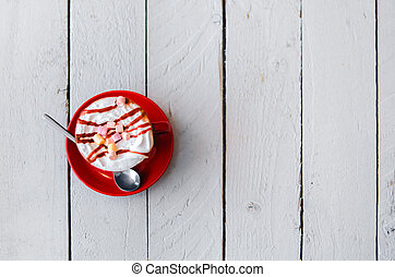 Red cup with coffee and cream on a beautiful white wooden