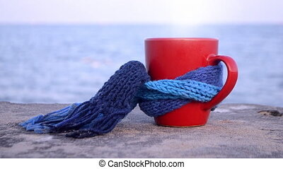Red cup with hot coffee tea and steam, tied with blue ...