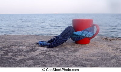 Red cup with hot coffee tea, tied with blue knitted scarf stands on stone surface near ocean sea waves close-up. Red cup mug coffe is located on concrete surface sea waves on background horizon.