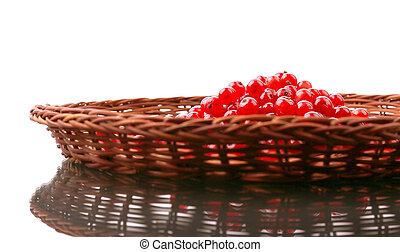 Red currant in a wooden basket isolated on a white background. A group of red berries. Sour and juicy berries for summer diets.