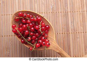 Red currant in wooden spoon