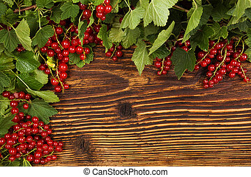 Red currant on wooden background.