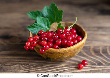 Red currant with leaves in bowl on rustic wooden table