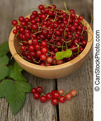 red currants and leaves in a wooden  bowl against brown background