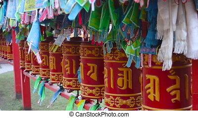 red cylinders with Buddhist mantras and yellow flags