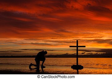 Red Dawn Praying - Man kneeling by a cross as the sun lights...