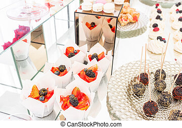 Red delicious muffin with blackberries and blueberries. Candy bar with a lot of desserts, meringue, cupcake, fruit and sweet cakes. Sweet table for birthday or wedding.