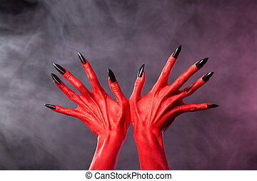 Red devil hands with sharp black nails, extreme body-art