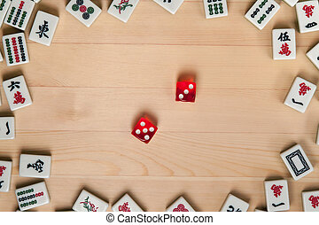 Red dice and bones (tiles) for mahjong on a light brown wooden background.