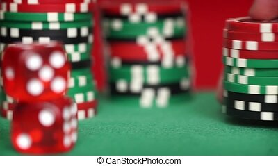 Red dice and casino chips on green table