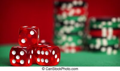 Red dice and casino chips rotation on green table