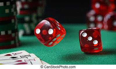 Red dice, casino chips, cards on green felt