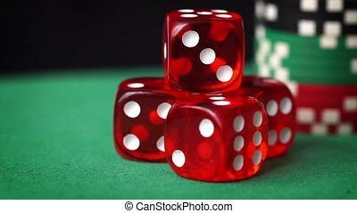 Red dice, casino chips, cards rotation on green felt