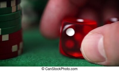 Red dice in hand and casino chips on green table