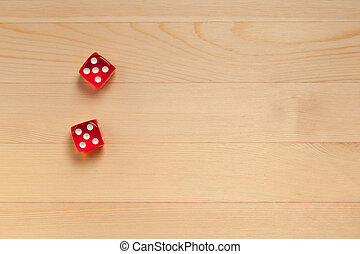 Red dice on a light brown wooden background. Discarded 10 (5 and 5)