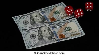 Red Dice rolling on Dollar Bills against Black Background, slow motion 4K