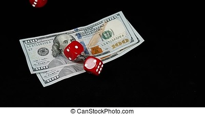 Red Dice rolling on Dollar Bills against Black Background, slow motion 4K