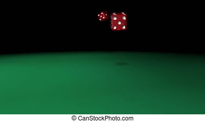 Red dice rolling on green casino table.