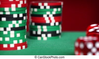 Red dice rolls and casino chips on green table