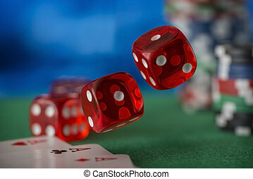 Red dice rotates and will fall 1, casino chips, cards on green felt