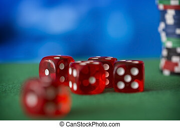 Red dice rotates on green felt, casino chips and cards