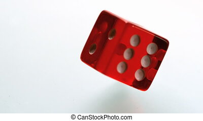 Red dice spinning and settling on white surface in slow motion