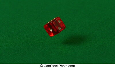 Red dice spinning on casino table in slow motion