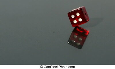 Red dice spinning on reflective surface in slow motion