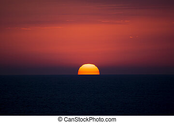 Red disk of the sun. Sea sunset.