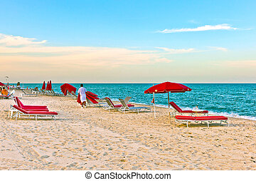 red divan beds in sunset light at the beach