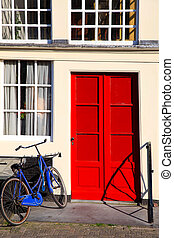 Red door and blue bicycle in old european house, Amsterdam.
