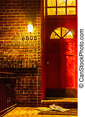 Red door on brick wall, side of a house at night with hanging lamp and newspaper