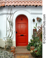 Red arched door in a white stucco building front