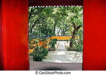 Red door revealing a beautiful  courtyard of a buddhist temple in Putuo Shan, China