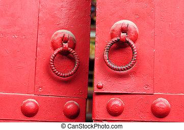 Red door with iron doorknobs