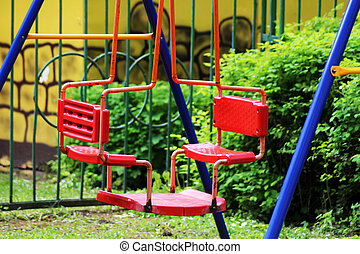Red double swing for children in the Park