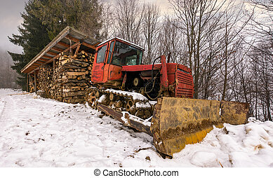 red dozer in snow near the wood shed. lovely rural scenery...